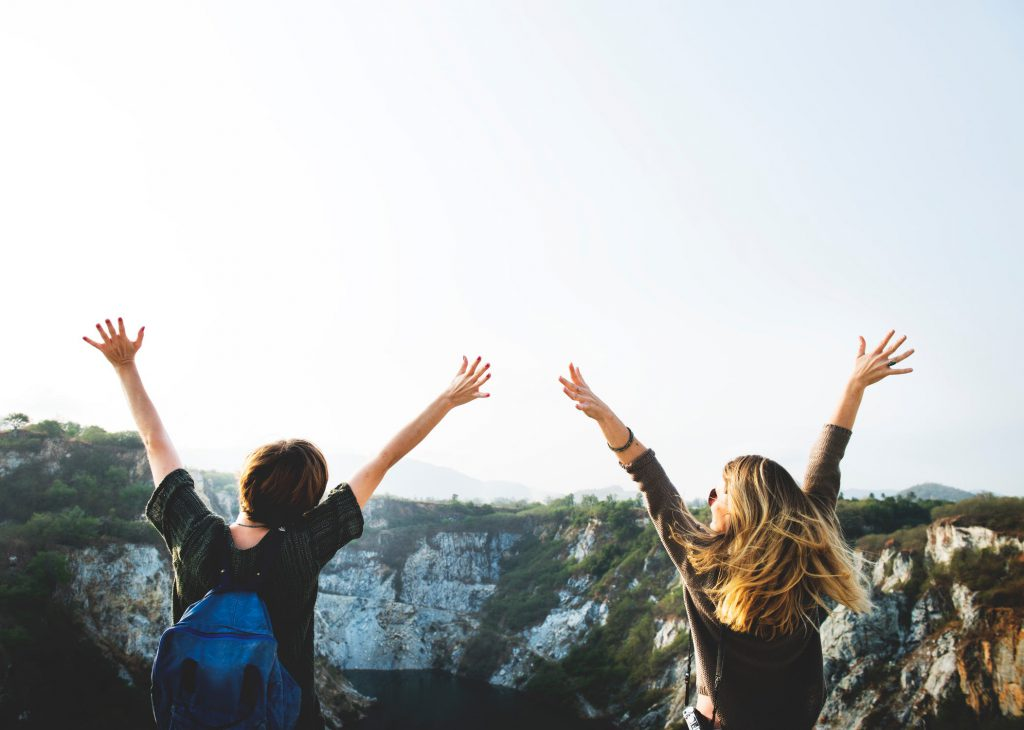 two friends with hands raised facing pretty landscape