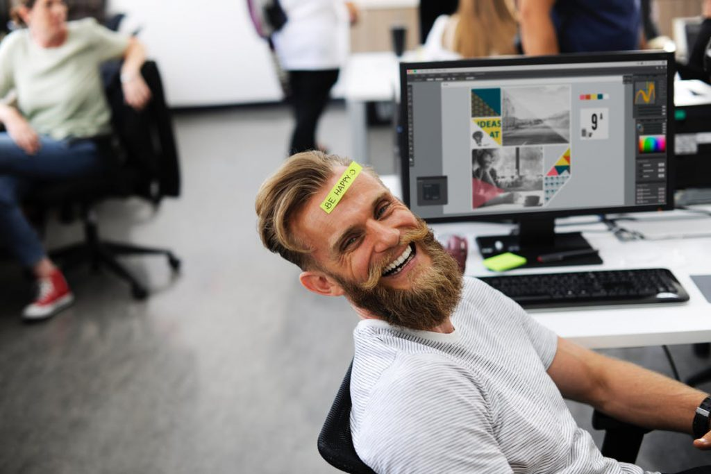 guy with beard in office smiling ear to ear